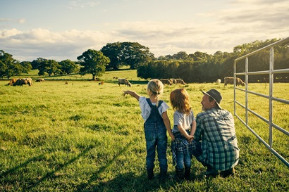 A family look out at livestock in a paddock.
