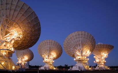 The back of five large white radio telescope dishes, lit up at night