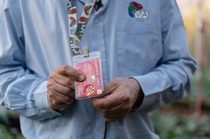 We see a close up of a man's torso. He wears a blue shirt, and his holding a red card in a plastic sleeve towards the camera. The card hangs from a lanyard around his neck.