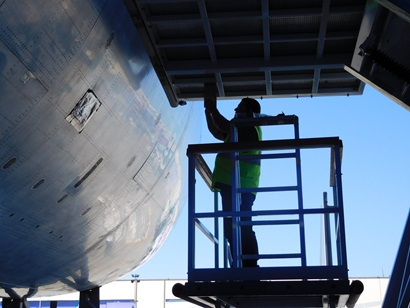 Image shows a man in a yellow hi-vis vest standing on a raised platform. The man is working on a aircraft fuselage.