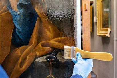 Image shows a gloved hand applying a clear resin to an artwork with a wooden and bristle brush. The sections of the artwork with resin appear wet. The artwork shows folds of fabric in brown and blue colours. In the background other images hang on the wall suggestive of an art gallery.