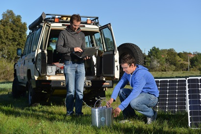 Two scientists and research equipment in a field.