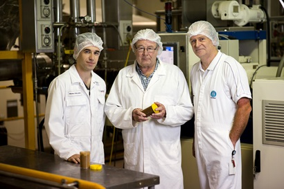 Three men wearing white overalls and hair nets standing in a processing facility.