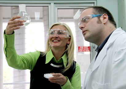 Larissa Bright holding up a flask of UV fillters with Dr Mark York