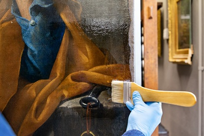 Hand applies a varnish resin onto a masterpiece painting with a thick soft brush