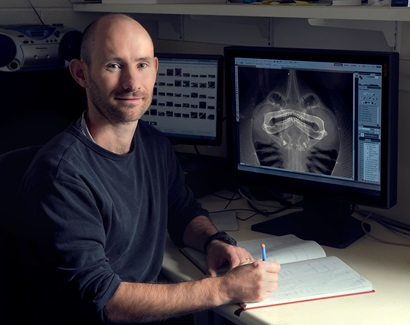 John Pogonoski sitting at desk with a screen in the background displaying a digital radiograph