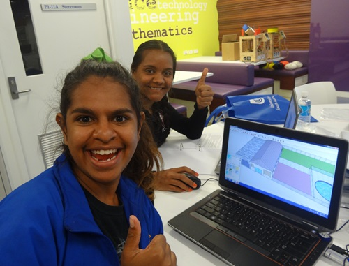 Smiling Indigenous students using a laptop