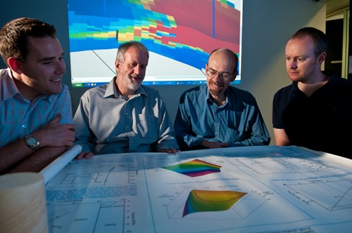 Four male researchers, Martin Leahy, Lincoln Paterson, Jonathan Ennis-King and Chris Green, seated around table covered with research diagrams with projection of geological model in background.