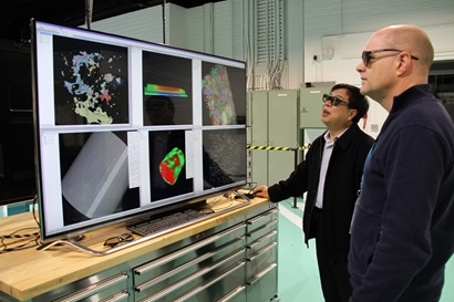 Two men standing in front of a large computer screen showing Lab 22 technology in use.