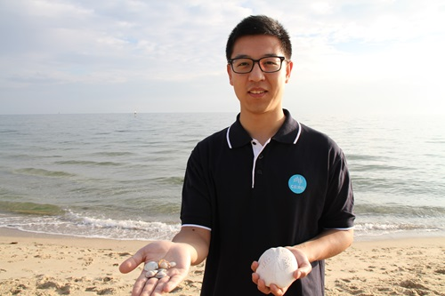 Dr Kang Liang holding an assortment of small seashells in one hand and a large seashell in the other.