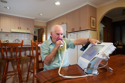 Man using the breathing apparatus of the home monitoring telehealth device.