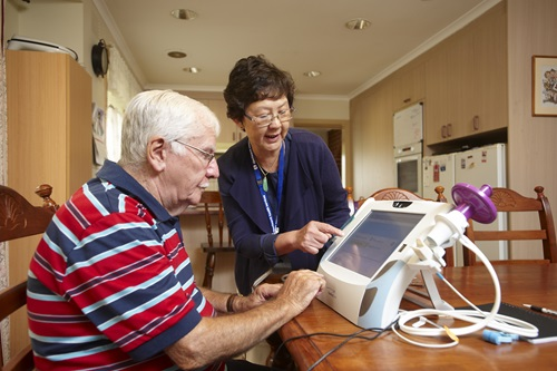 Telehealth nurse shows a patient how to use the home monitoring system.