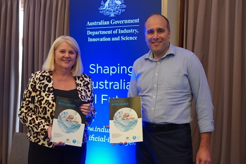 Karen Andrews and Stefan Hajkowicz holding a copy of the AI roadmap report.