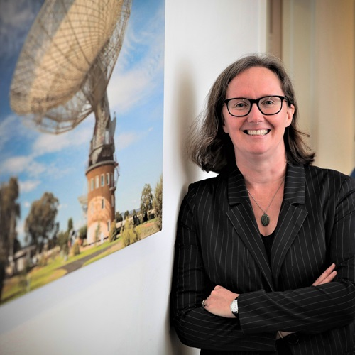 Dr Sarah Pearce standing in front of a photograph of a radio telescope.