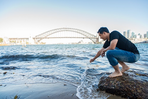 Scientist scoops water out of Sydney Harbour, with the Harbour Bridge in the background.