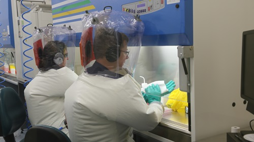Two people working in a laboratory in protective suits.
