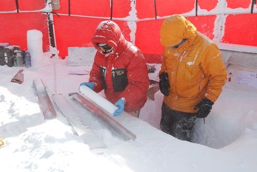 Two people in extreme weather outfits looking at an ice core.