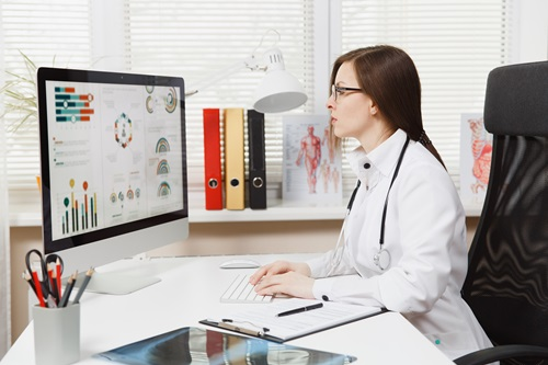 Clinician in a white coat sitting at a desk using the medtech platform on a computer.