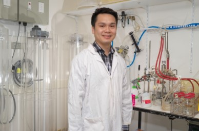 Kim Lee Chang wearing a white lab coat standing next to equipment in a laboratory.