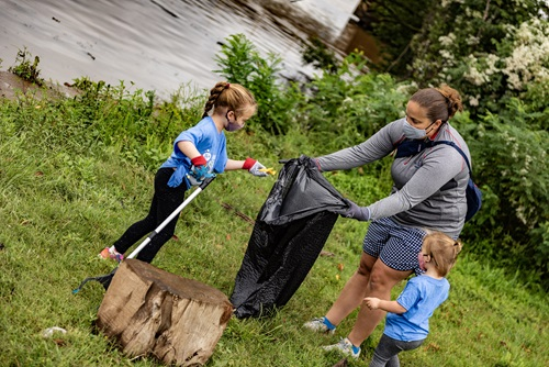 Women holding garbage bag with two children collecting rubbish