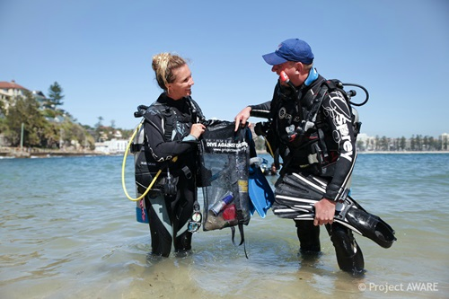 Two divers stand in shallow water holding a bag with plastic pollution they have collected