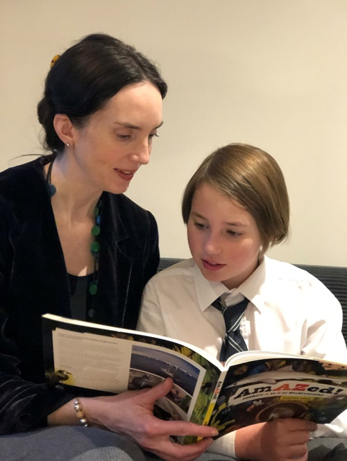 Mother and son sit on couch with book