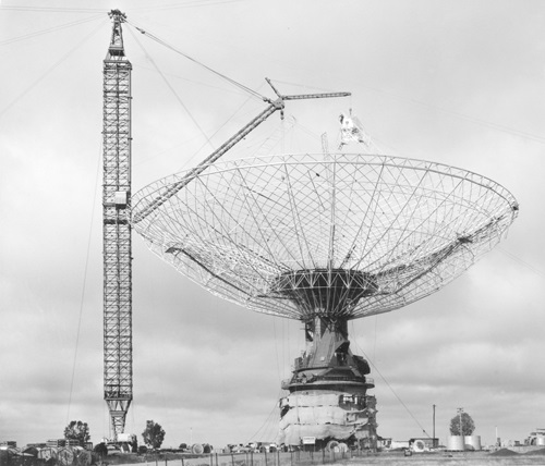 Black and whte photgraph of the Parkes telescope under partial constructions with crane tower next to the frame of the dish section.