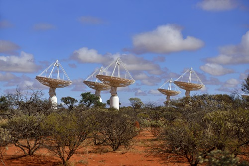 Six of the ASKAP telescopes shown during the day surrounded by bushland.