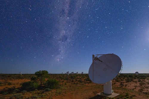 Close up of one of the ASKAP telescopes in the foreground shown during the night with several others in the distance.