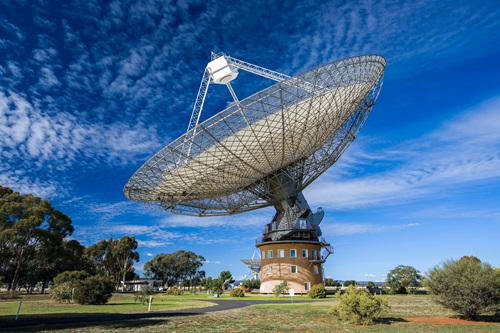 CSIRO Parkes Wiradjuri telescope during the day with blue sky and scattered clouds as the backdrop.