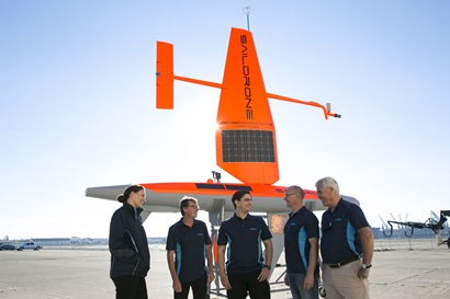 Five CSIRO staff stand in-front of an orange Saildrone