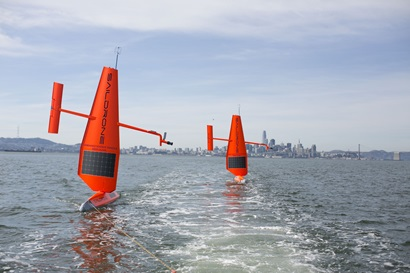 Two Saildrones are sailing in the water. A city can be seen in the distance.