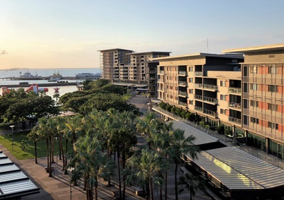 view of waterfront development with palm trees in the foreground and multistory apartments