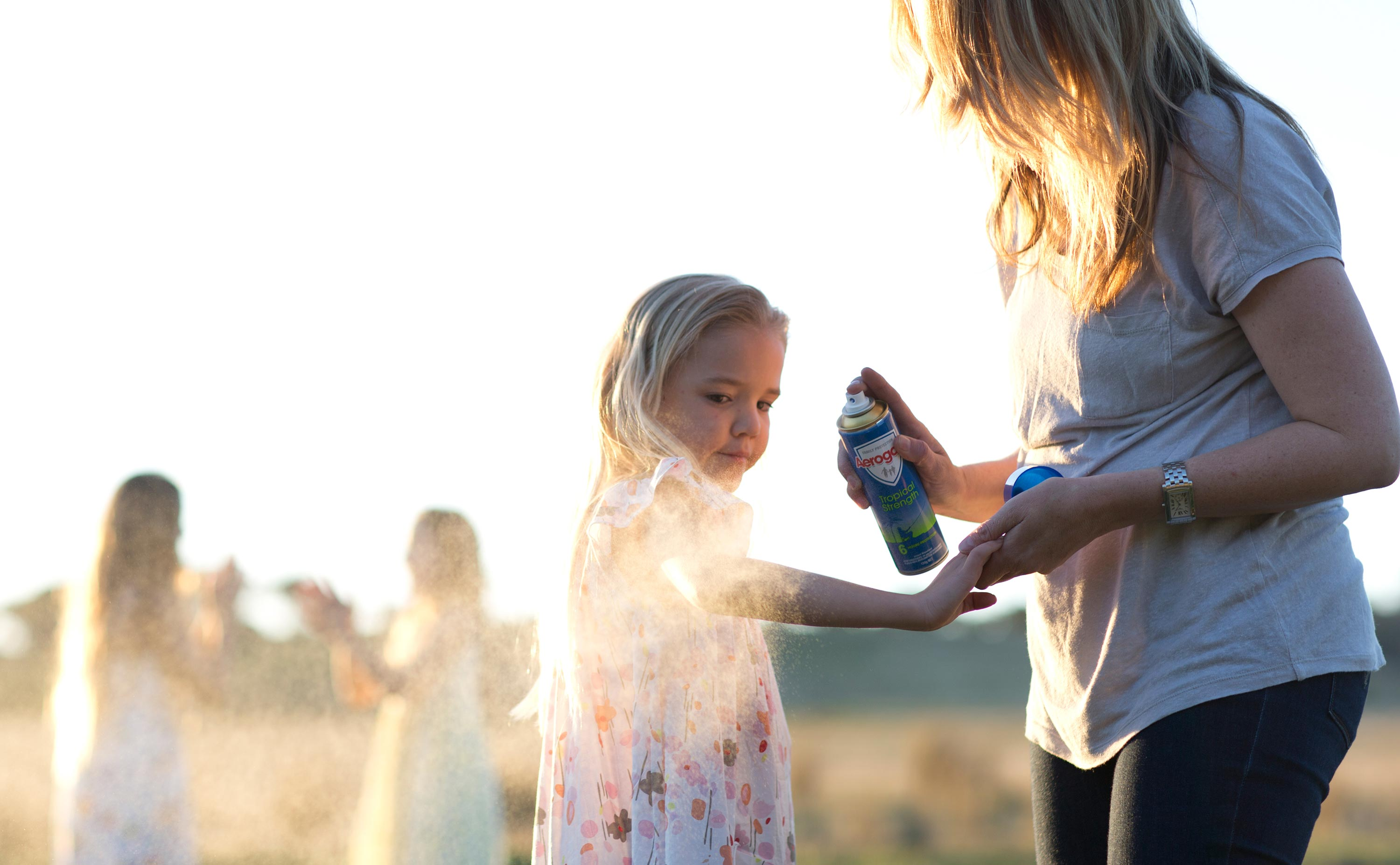 Woman spraying her daughter with Aerogard, an insect repellant