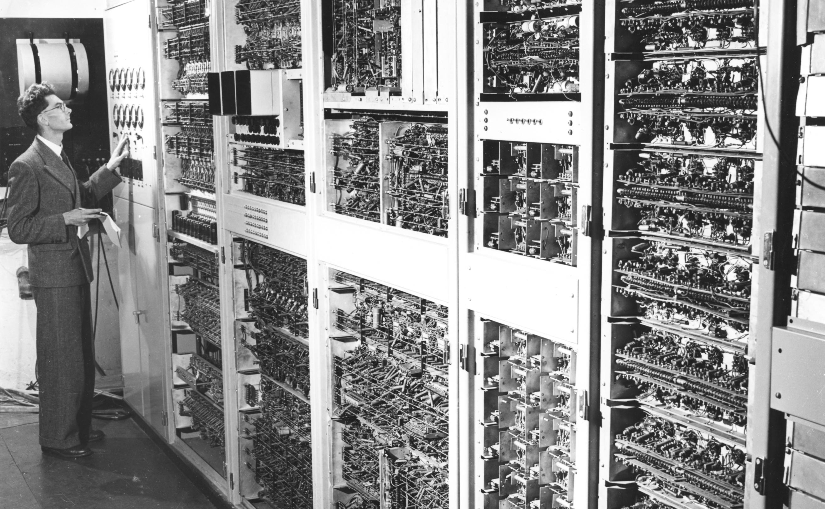 Man standing in from of the first computer at CSIRO