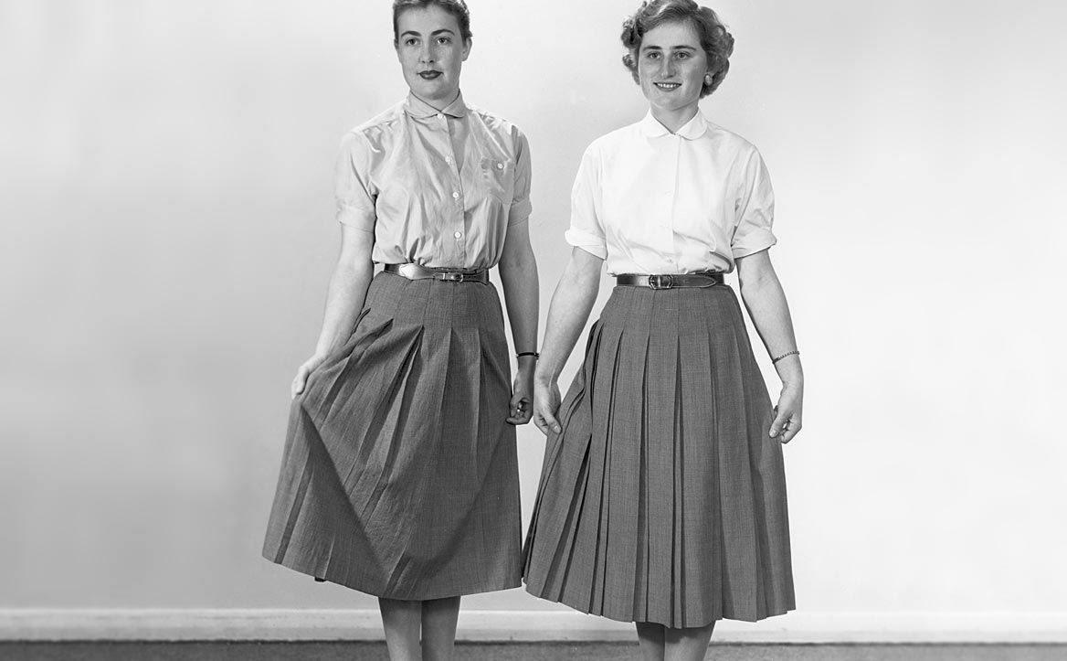 Women in the 1960s showing off their pleated skirts