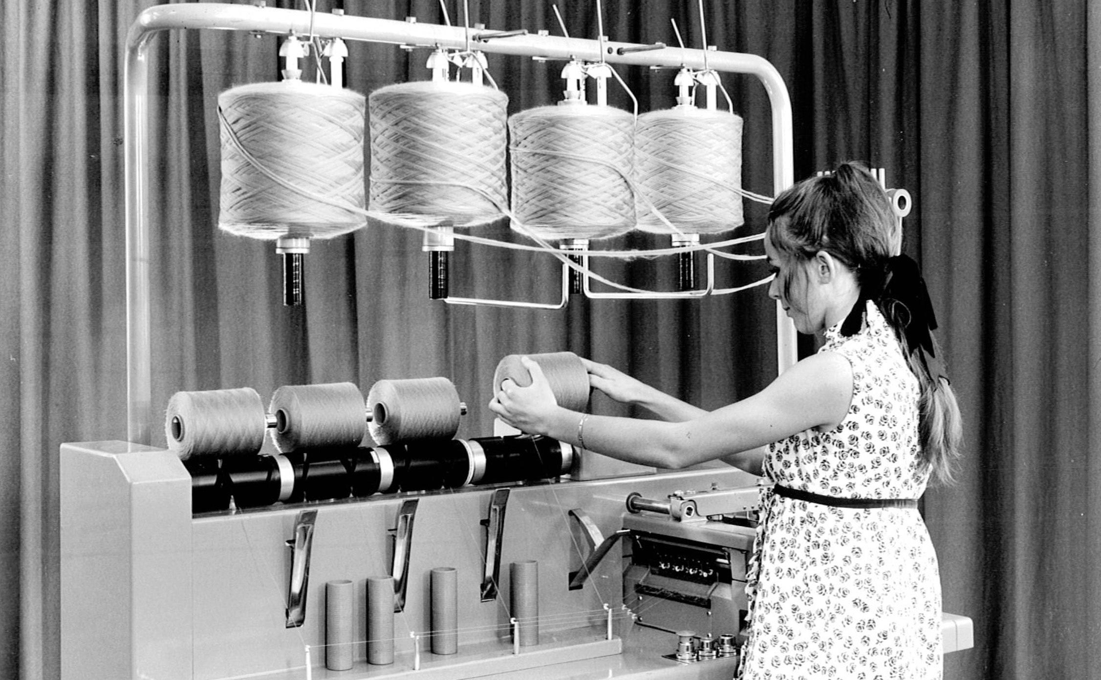 Woman standing in front of a self twisting yarn machine, black and white from the 1960s