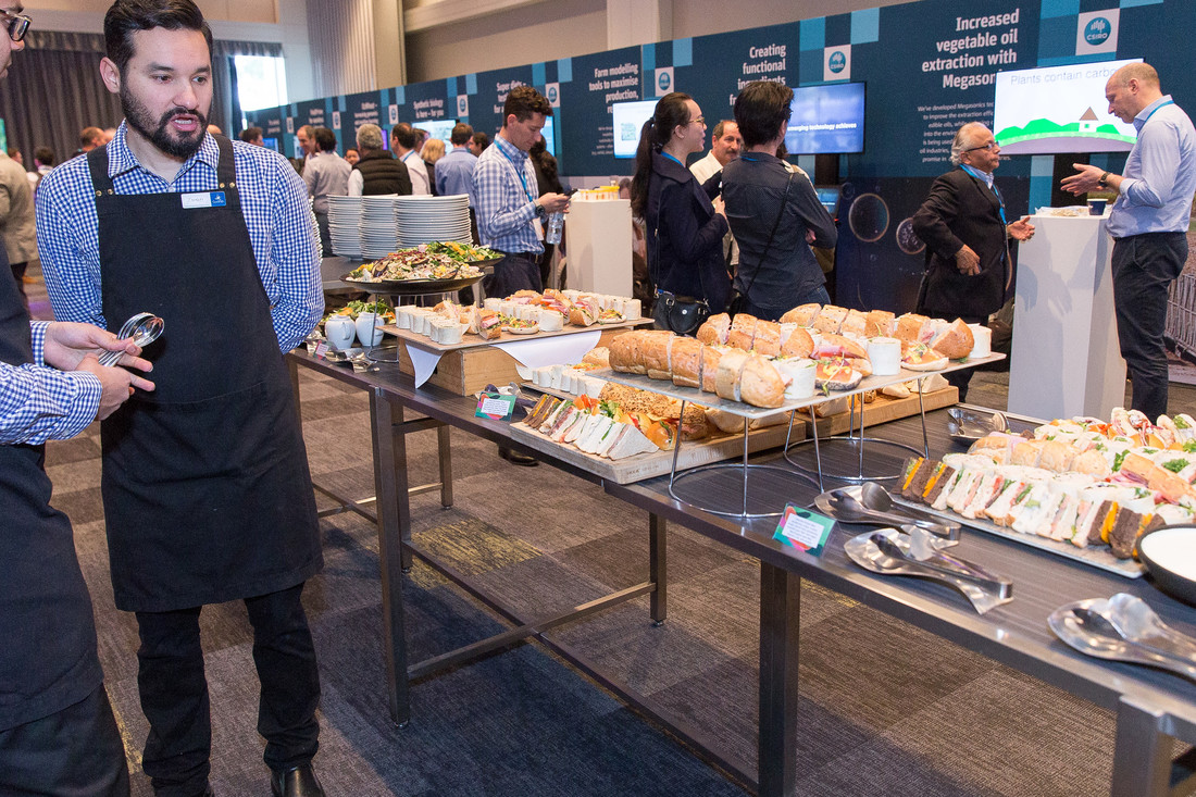 A waiter stands in front of a table of sandwiches, with exhibits and people mingling in the background