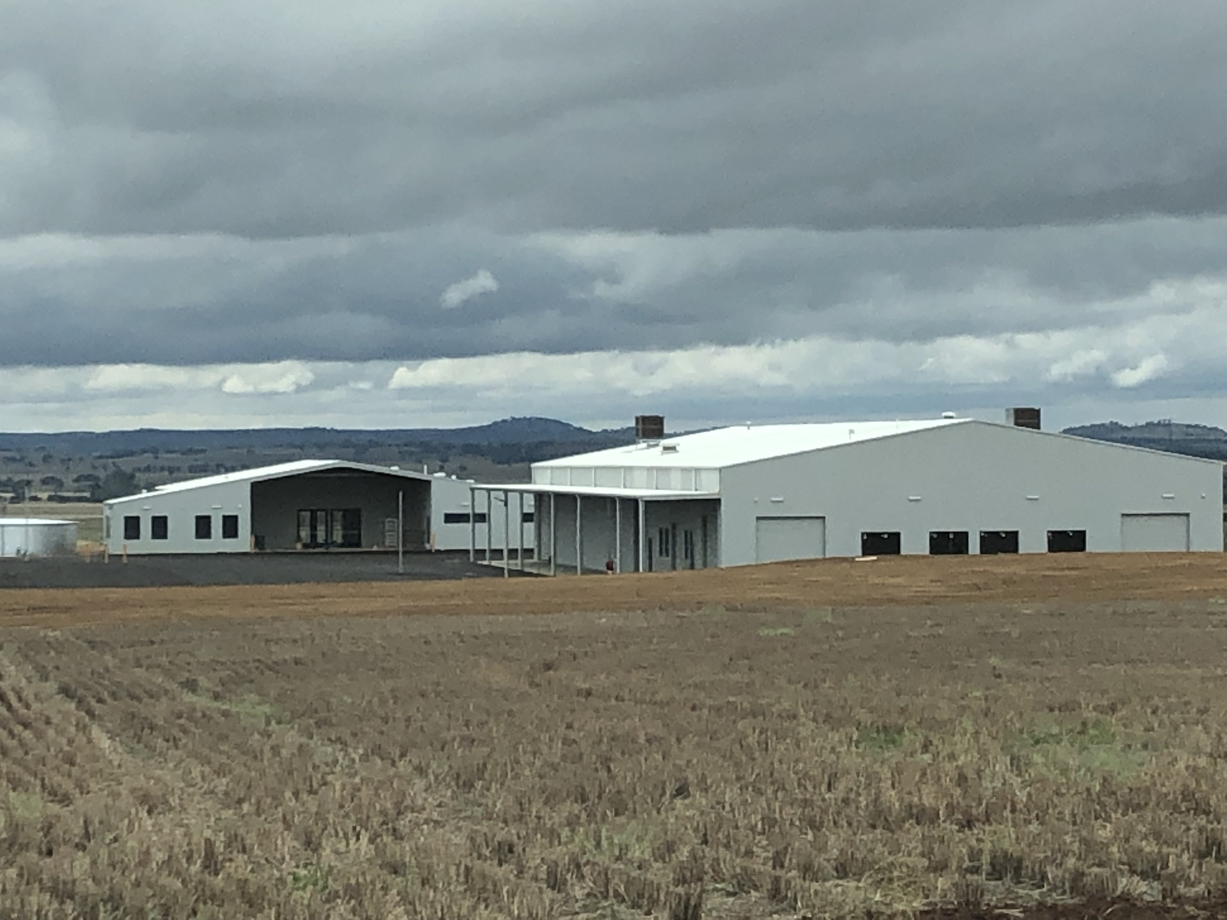 Two large new sheds with a field in the foreground