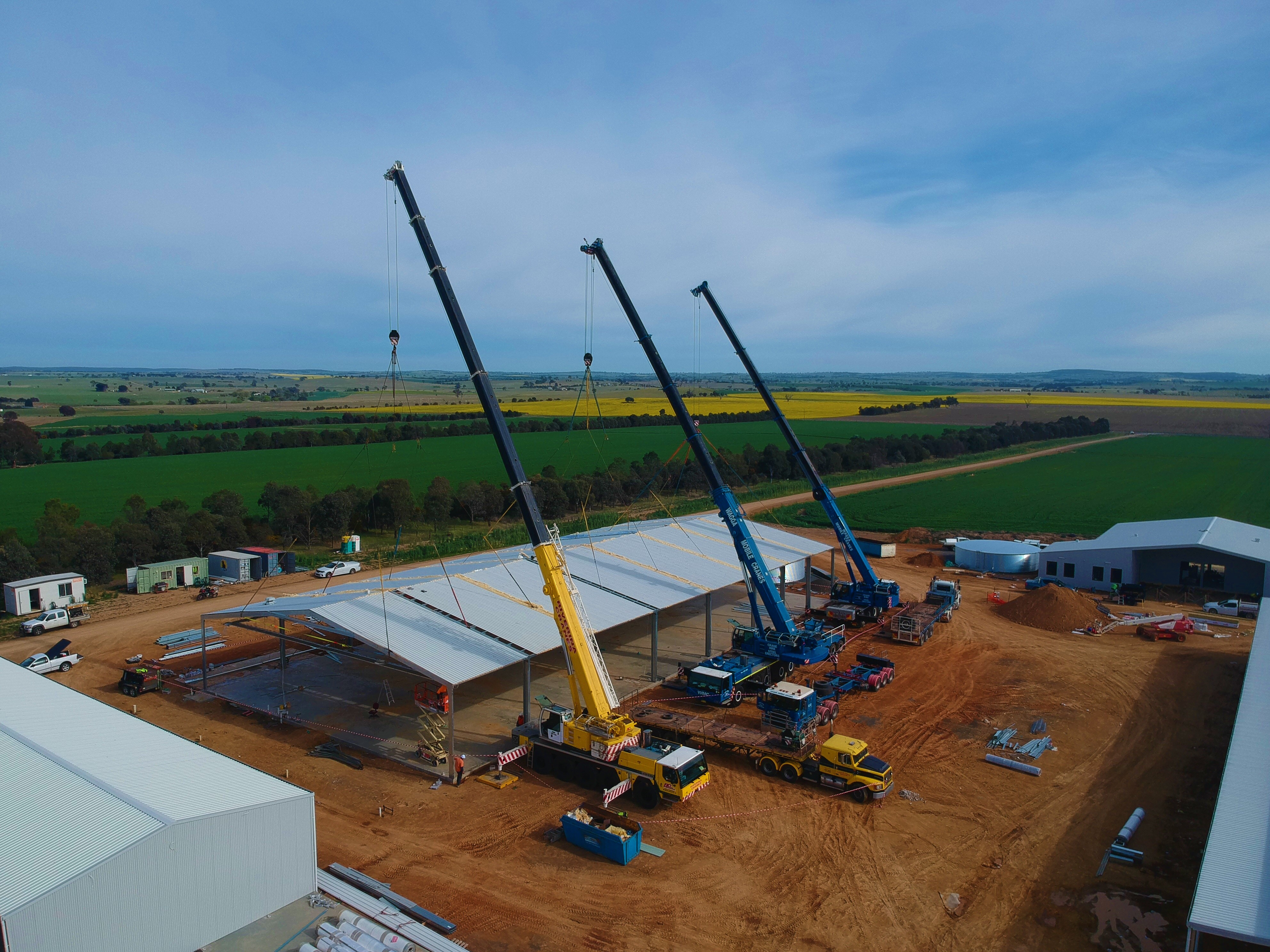 Three cranes lift the roof of a workshop into position