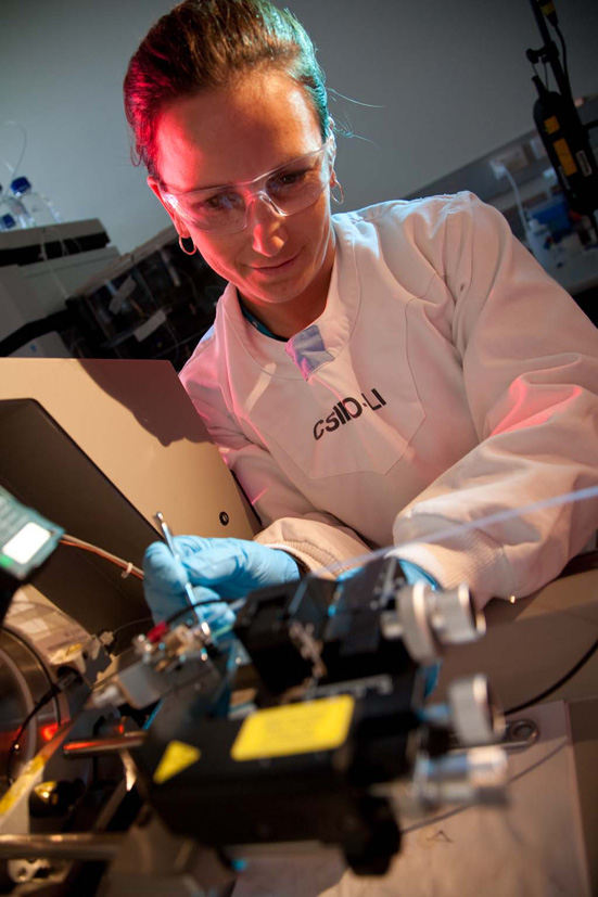 A female scientist puts a sample into a machine to analyse it