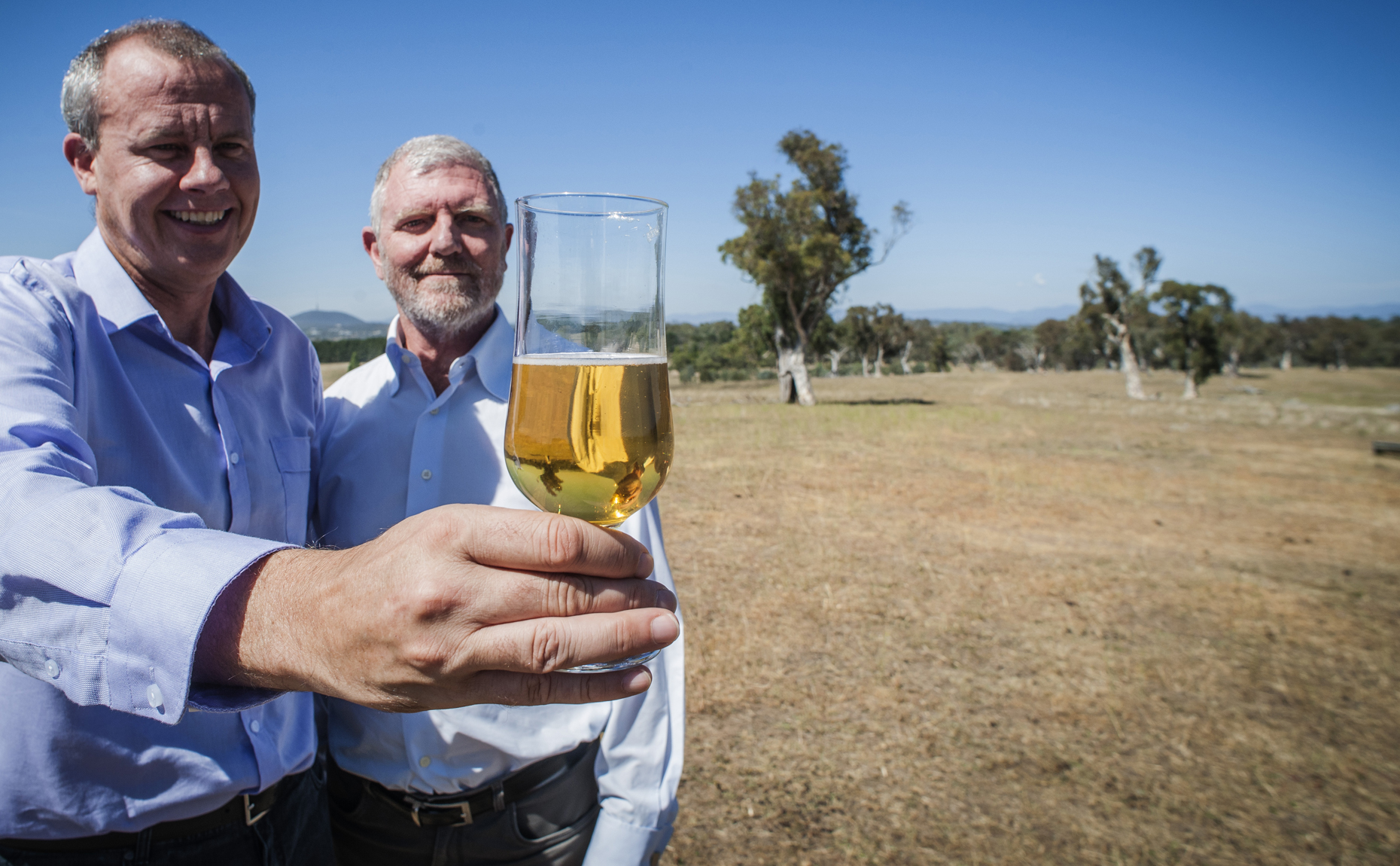 Dr Crispin Howitt and Dr Phil Larkin from the Kebari barley team stand holding a glass of beer, an example of a product made with Kebari barley, in a field.