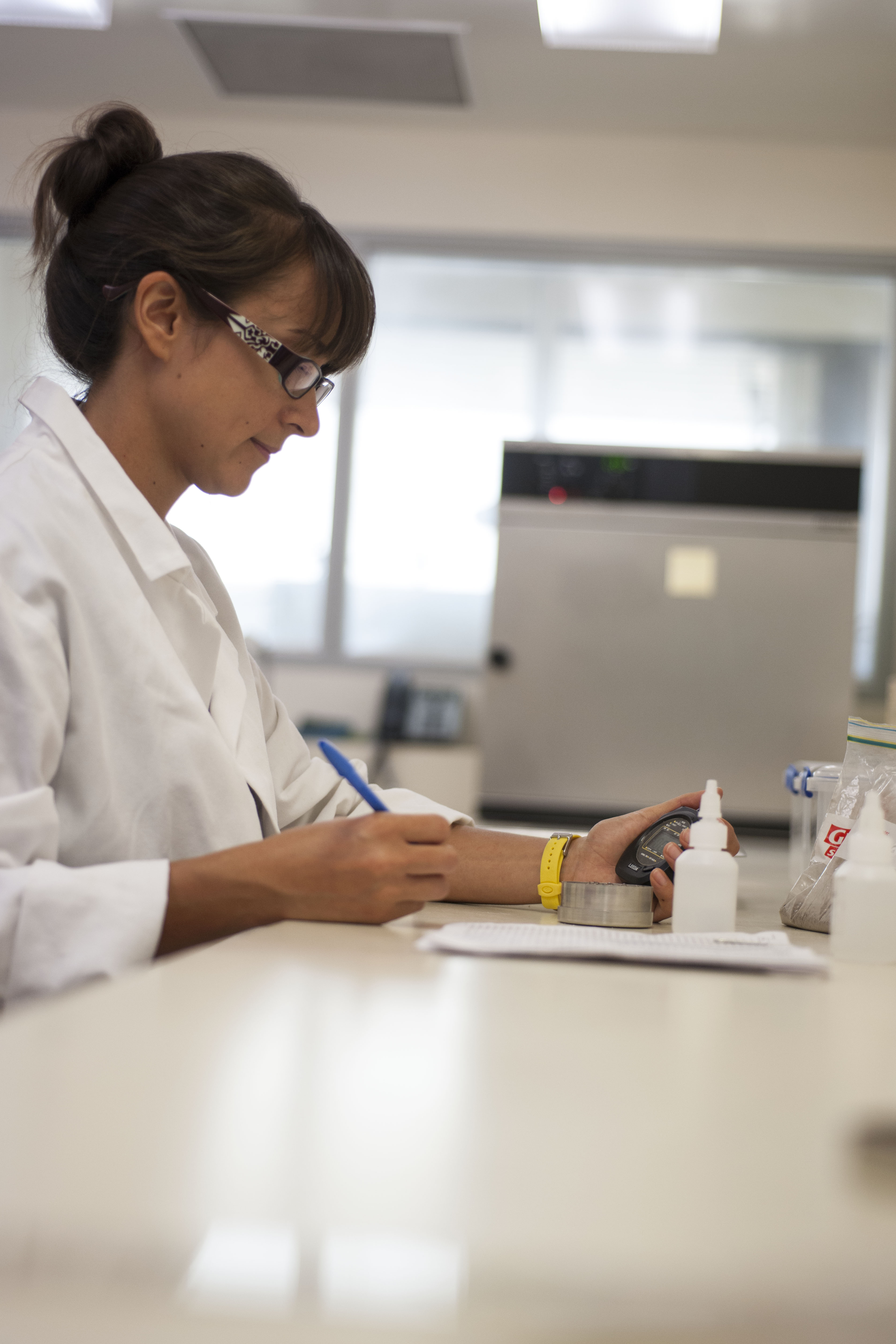 A female CSIRO scientist in a white lab coat and glasses sitting at a white lab bench holding a blue pen and black stopwatch watching a small tin of soil on the bench