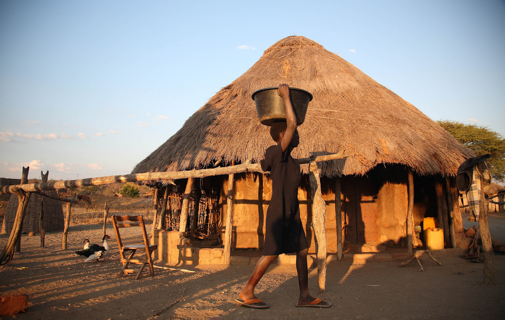Woman walks past a simple hut in a village in Africa carrying a container on her head