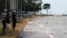 Three people observe the King tide event at Shorncliffe in 2009