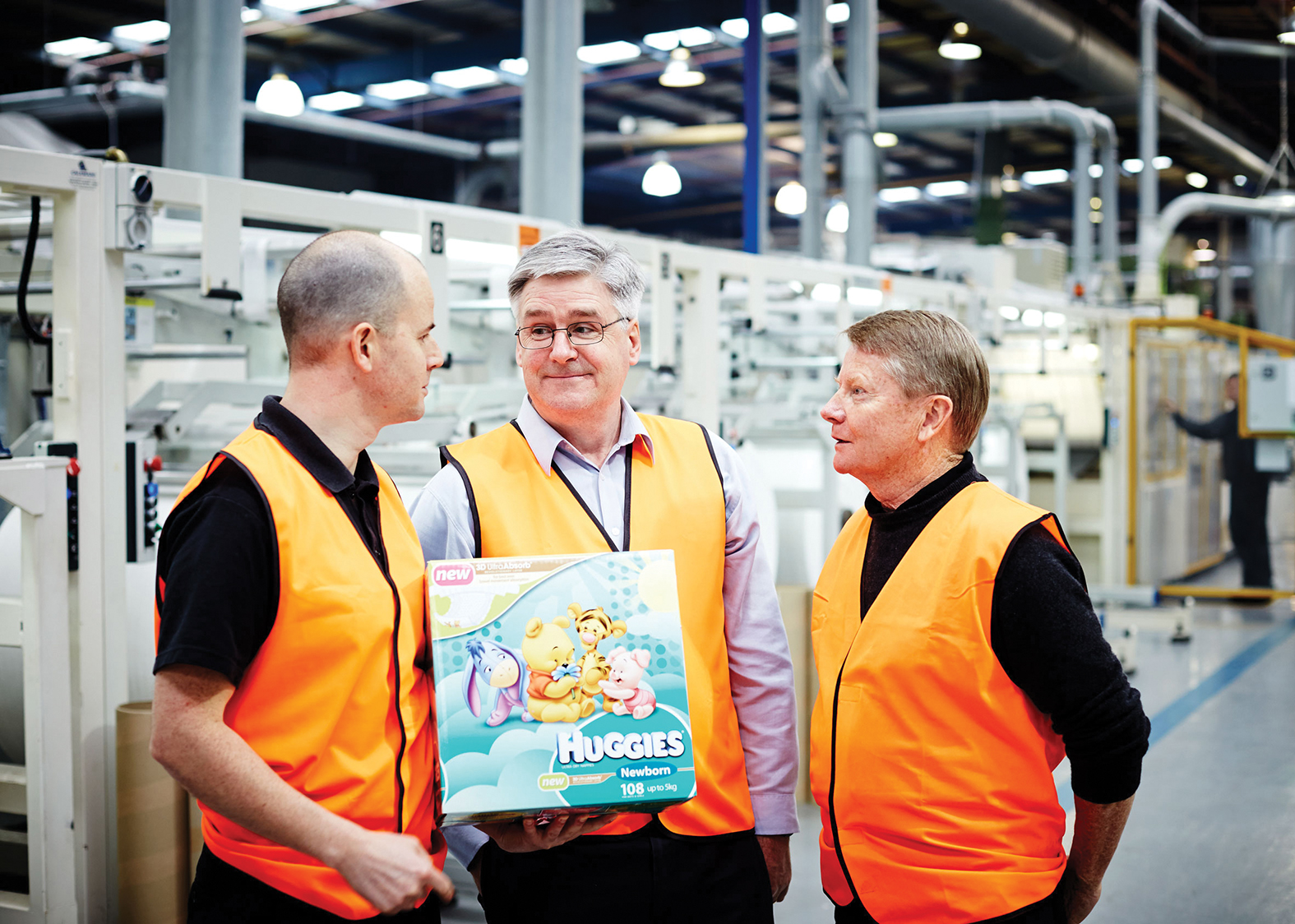 Andy Butler, Phil Butler and Dr Niall Finn standing in front of warehouse factory equipment at Textor's Tullamarine premises in Victoria.