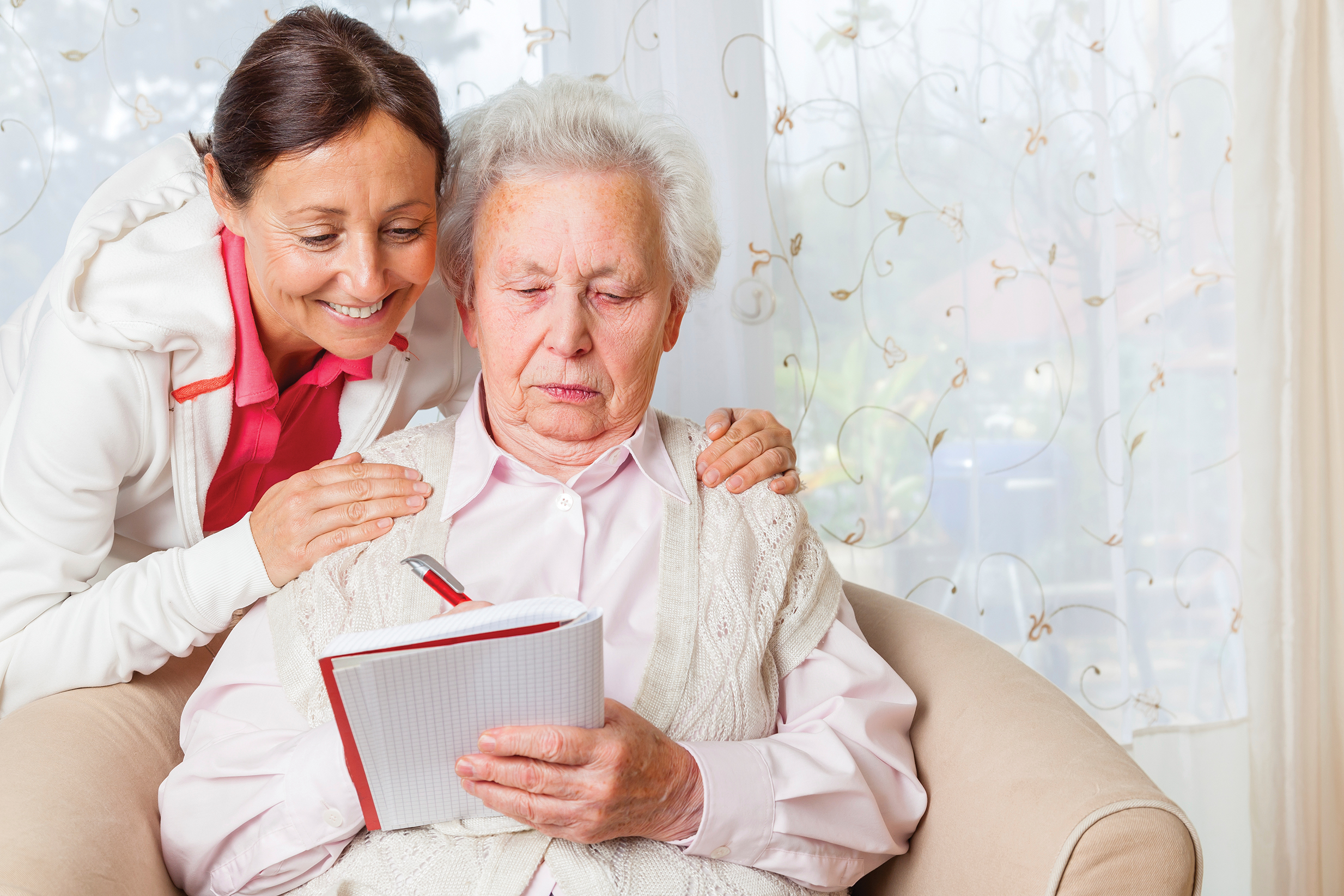 Young woman leaning over shoulder of elderly woman writing on a notepad.