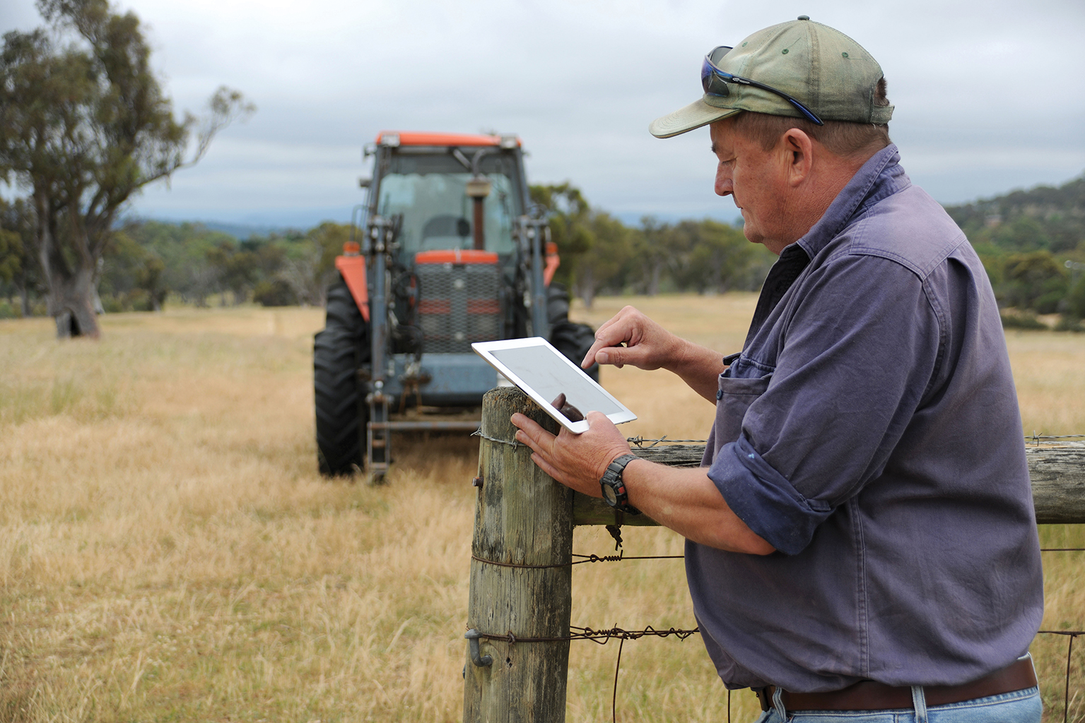Farmer standing against a farm fene post using an iPad, with a tractor in the background.