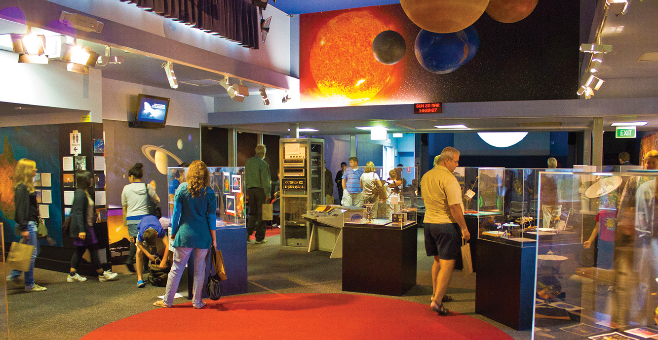People looking at display boxes in the visitor centre at the Canberra Deep Space Communication Complex.