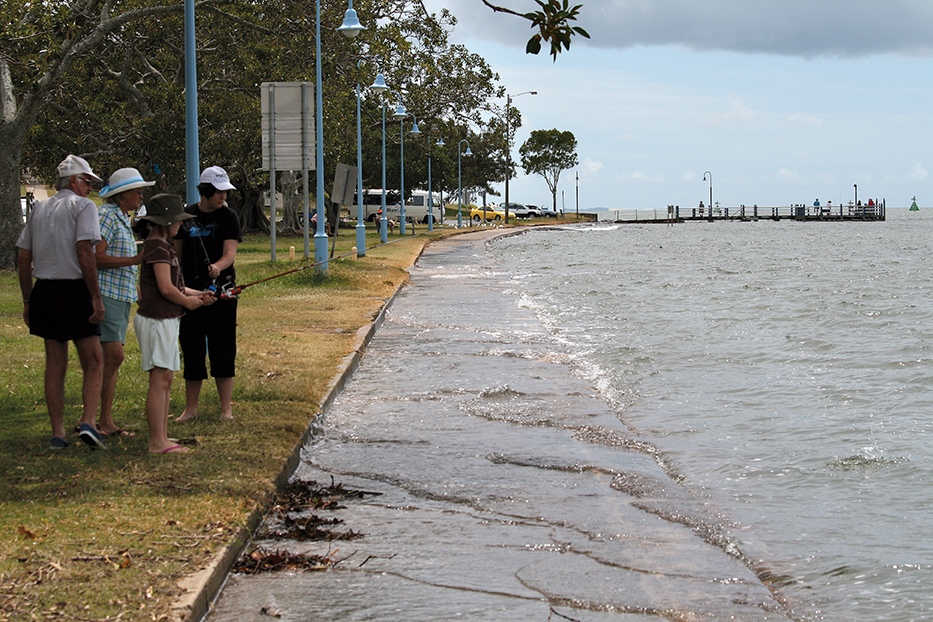 People standing next to water during a king tide event at Shorncliffe.
